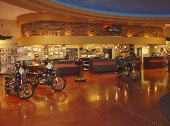 Motorcycles sitting on a stained concrete floor in front of a counter.