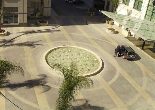 Circular concrete fountain that has been designed with the circular patio in mind that surrounds it.