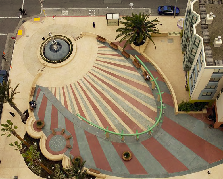 An aerial view of an expansive concrete street corner that has been colored with alternating ribbons of blue, white and red.