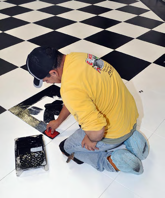 A contractor applies the black color by hand on his knees.