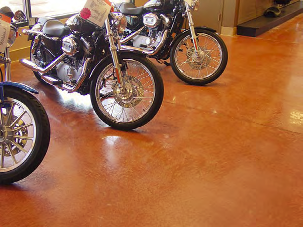 Three motorcycles sitting on a brown concrete stained floor.