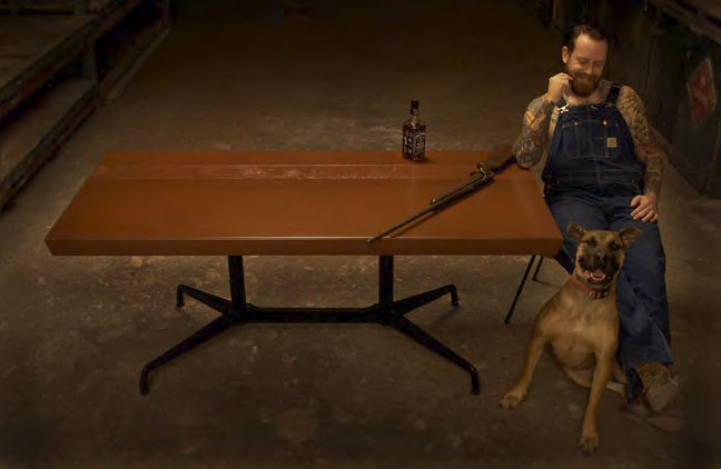 Brandon Gore sits at his concrete table with a rifle, whiskey and his pup.