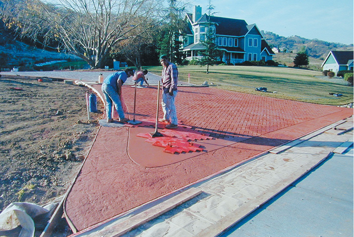 Cafting decorative concrete by stamping a concrete driveway apron using tampers