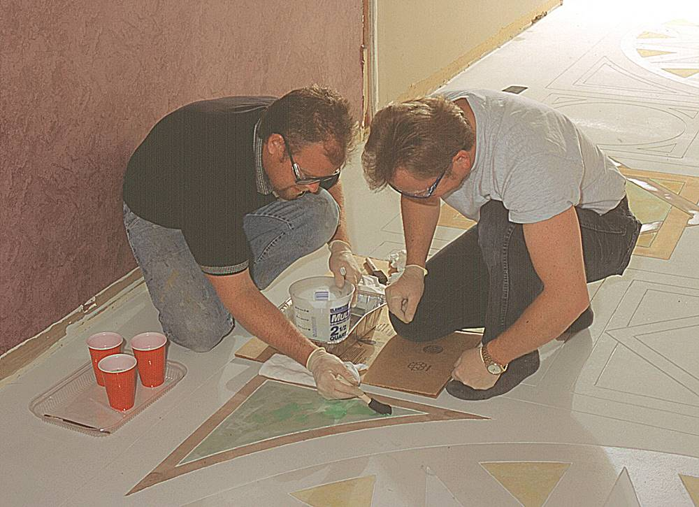 Two men staining within a stencil. Water based stains are a versatile tool to use for floors.