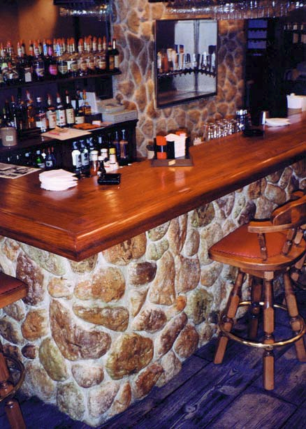 A bar counter with decorative stones below that were created with formliners, gives the look of a hand placed stone application