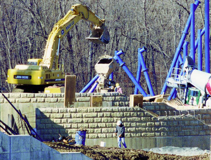 A John Deere backhoe moves concrete for a large vertical wall textured with formliners.