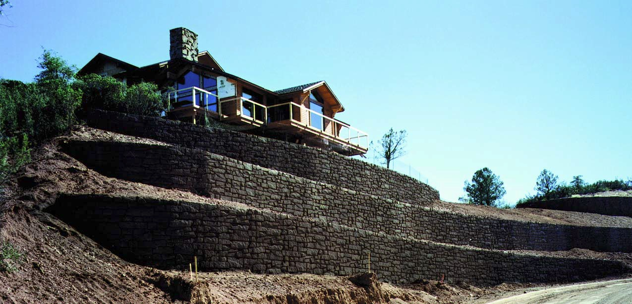 A large custom home with an expansive concrete retaining wall created using formliners to achieve decorative rock.