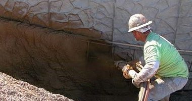 A concrete mason shoots shotcrete onto the wall with a pump.