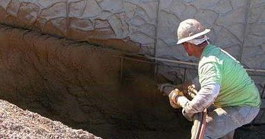 A concrete mason shoots shotcrete onto the wall with a pump.