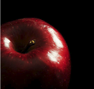 The apple is red, but because the surface is glossy, the light source is visible as a white highlight.