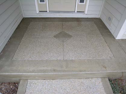 Concrete patio with inset exposed aggregate center.