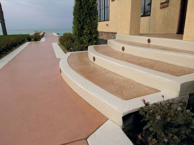 Integrally colored concrete walkway steps down patterned concrete stairway.