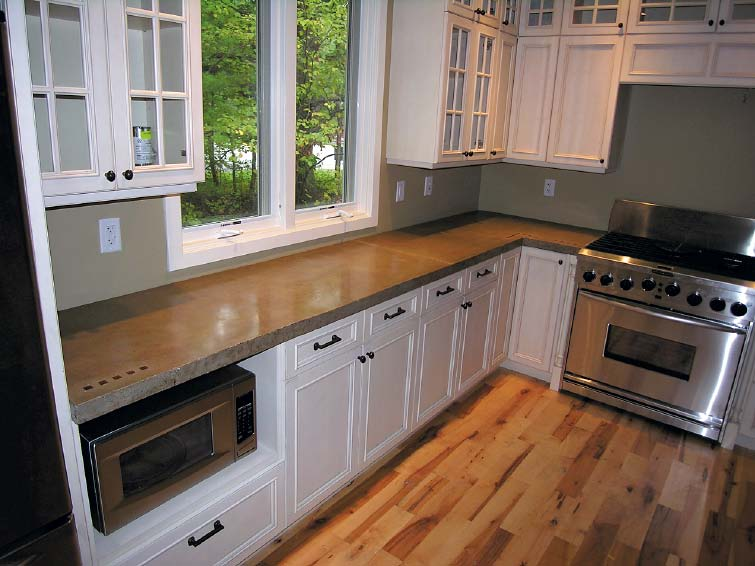 White kitchen cabinets with natural concrete countertops with inset items.