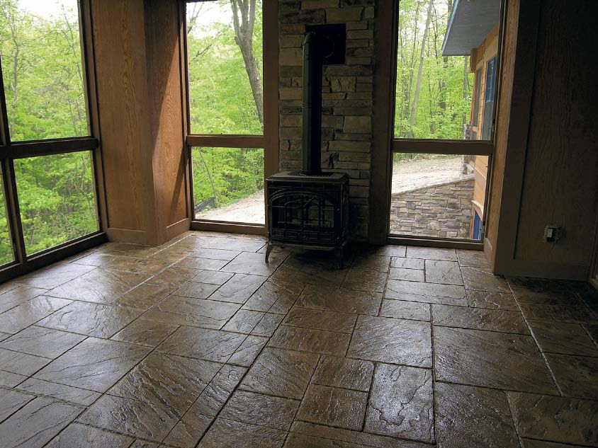 Living room with stamped concrete and a freestanding fire place.