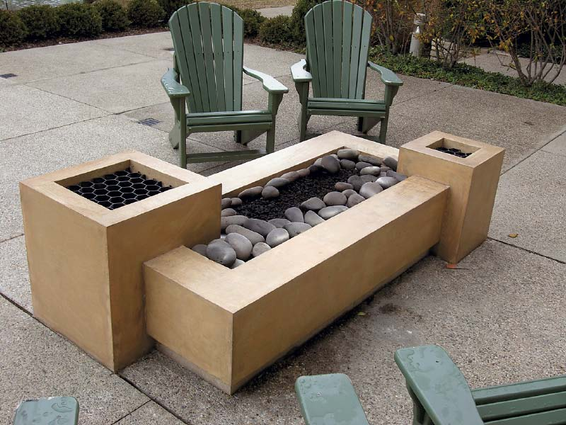 Rectangular stepped fire pit with river rock.