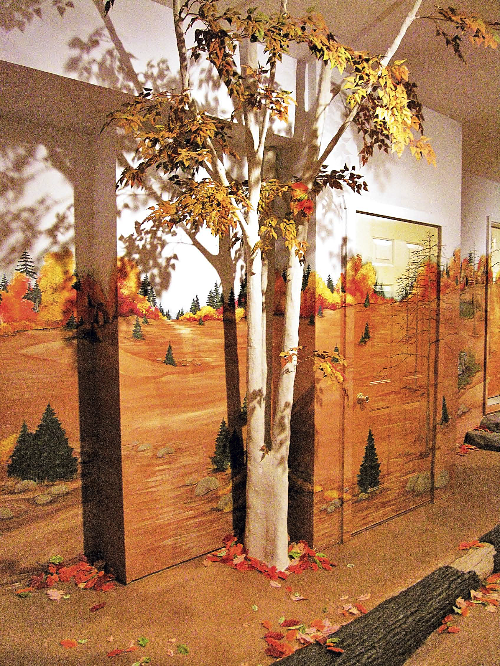 Poplar tree made of concrete stands in a room with a landscape mural on the wall that crosses over the door.