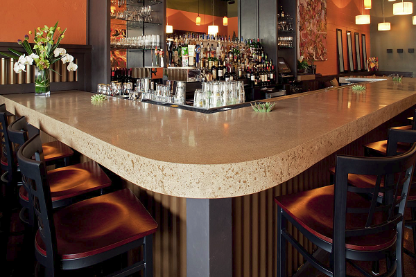Littlefield included four little wells along the edge of the bar to hold mirrors and floating candles in this concrete countertop that functions as a bartop