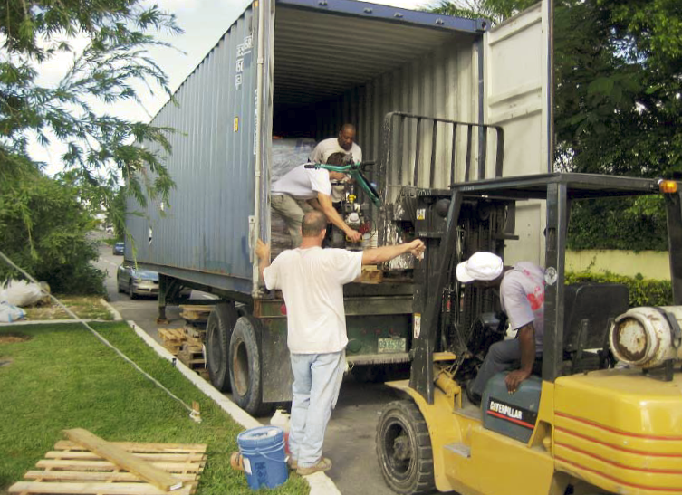 Three guys using a forklift to load the truck of supplies needed for an international project.