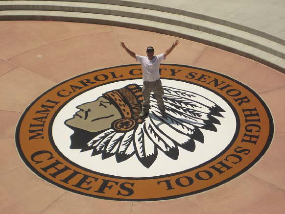 A person stands on the finished stencil a logo for a high school in Florida