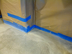 Using blue masking tape and brown masking paper when preparing to stain a concrete floor.