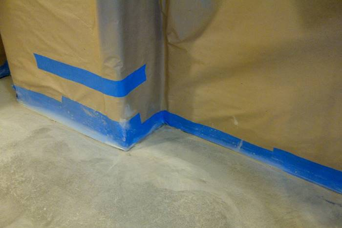 using paper and masking tape on walls and baseboards to prep for concrete staining