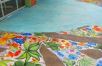 Concrete overlay in sea blue by Butterfield Color guides visitors to the entrance of an after school program in San Antonio, Texas.