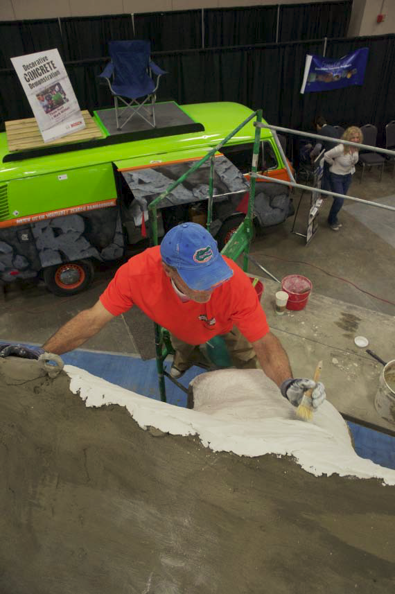 Artist Thom Hunt working in the details of the concrete dinosaur.