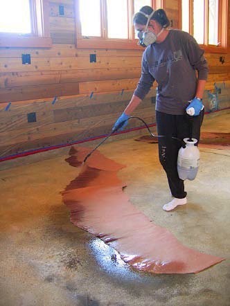 Concretist Brenda Walz uses an all-plastic, pump-up garden sprayer at a Martinez, Calif., home to apply stain along a stratalike torn paper edge and over scattered Ironite granules.