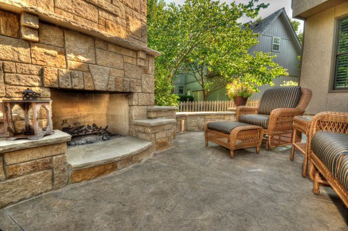 Stamped concrete patio with fiber optics during the daylight hours looks beautiful in front of a carved concrete outdoor fireplace.