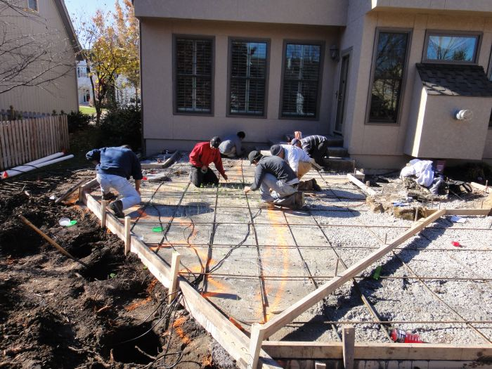 Concrete crew laying out fiber optics prior to placing and then stamping concrete in the formed area