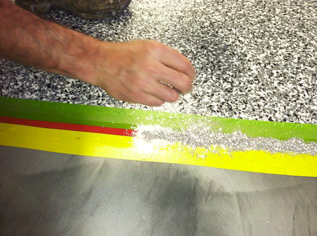 Applying metallic to this concrete floor with a red, yellow and green tape line.
