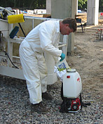 Man if full white coveralls filling a Hudson sprayer on a job site.