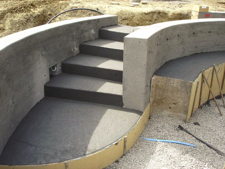 Concrete steps coming down from the grass to the concrete ceremony space.