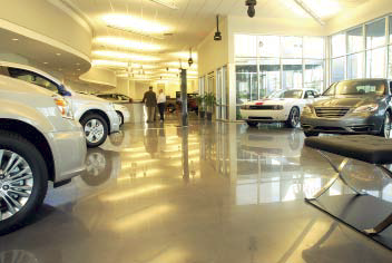 A car dealership that has been polished to highly reflect the cars sitting atop.