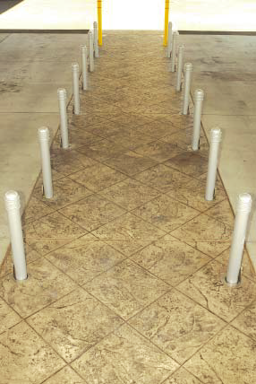 Stamped and stained concrete with posts that act as guides.
