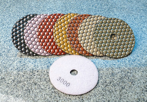 Dry polishing pads with a ceramic binder, shown here, can help prevent smearing and glazing.
