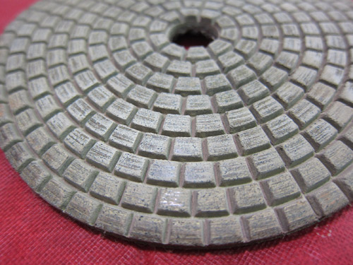 A dry polishing pad with a resin binder. Inexpensive pads can use soft resin binders that wear quickly. Buying a more expensive, higher-quality pad can save you money in the long run versus buying multiple cheaper pads.