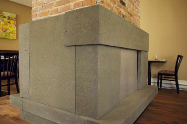A fireplace surround made of concrete that surrounds the brick chimney