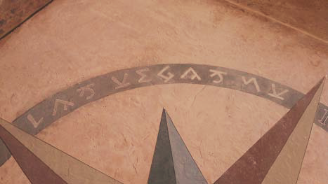 A close up of a compass rose stained onto concrete.