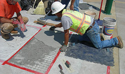 Construction worker replacing failed stamped overlay.