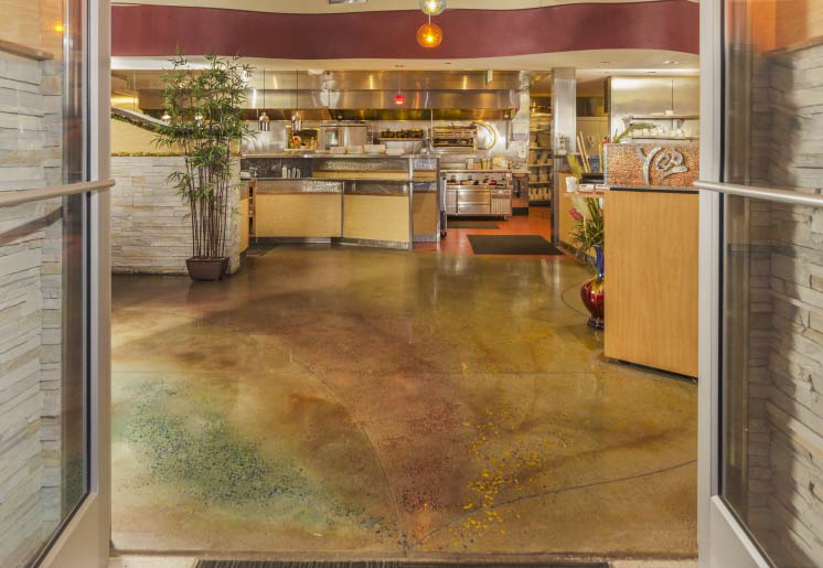 Stained concrete floor in a retail establishment that has browns, reds and greens.