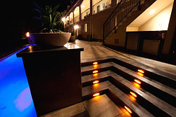 The steps are illuminated with inset lighting that features yellow, white and orange swirled glass with a copper frame, adding to the overall artistic feel of the area. The golden-yellow lights were designed to pop off of the grey concrete.