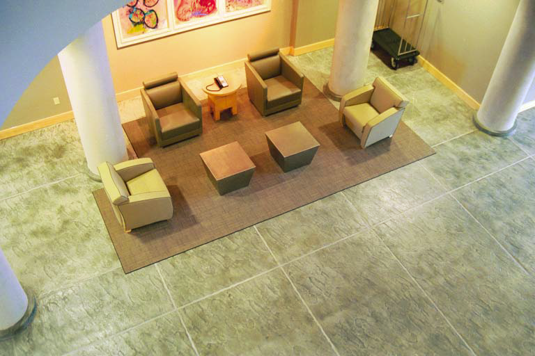 A look down on a greenish concrete floor in a lobby space.