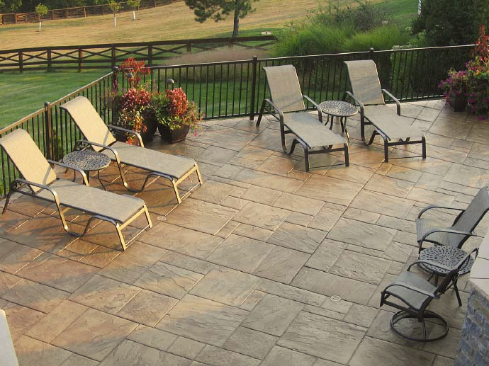 Stamped concrete outdoor deck with lounge chairs.