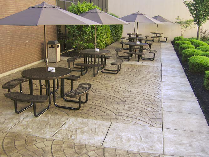 Picnic tables with umbrellas sitting on an outdoor patio complete with stamped concrete.