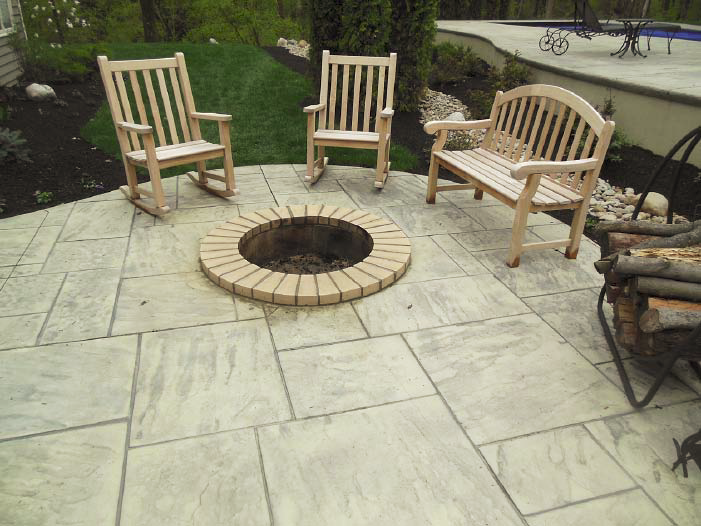 A concrete firepit surrounded by stamped concrete.