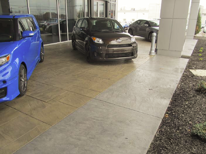 Cars parked on top of a concrete stamped patio outside a car dealership.