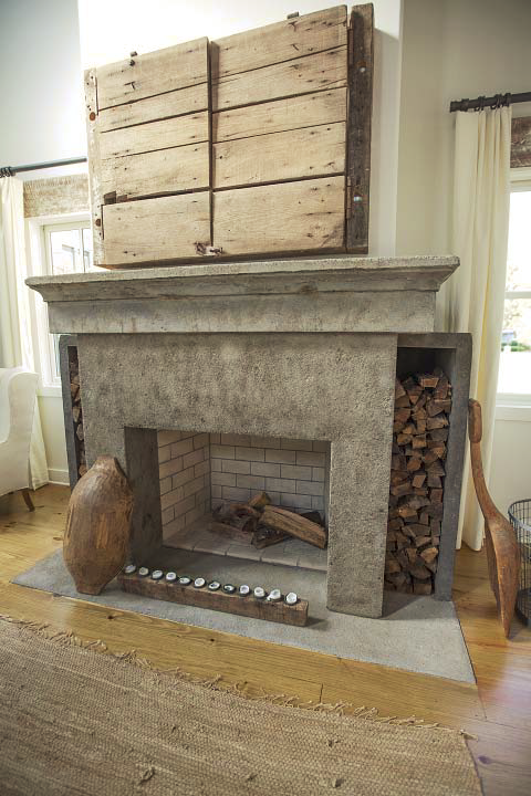 A concrete fireplace with firewood in shelves next it.
