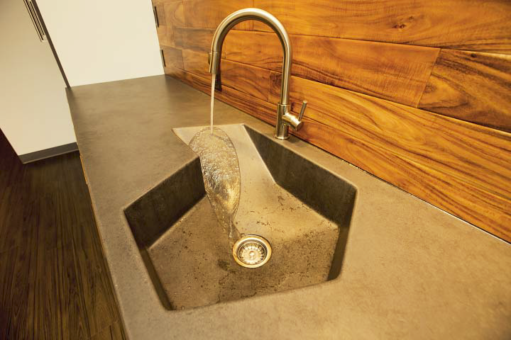 Concrete sink with an abstract shape and a slope toward the drain.