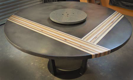 A concrete table in dark gray with ribbons of wood inlayed.